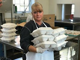Community Kitchen Assistant Rachel Nolan holds hot meals boxed and ready to go home with those who come to the soup kitchen daily.