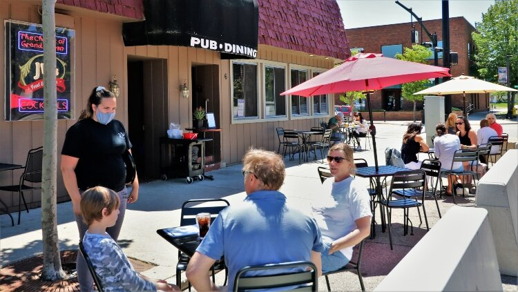 Customers at JW's Food and Spirits in Grand Haven take advantage of expanded outdoor seating into former parking spaces.