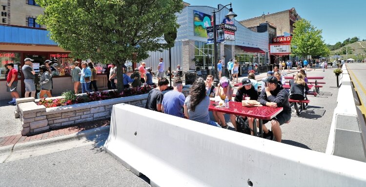 Downtown Grand Haven extends outdoor dining onto a barricaded section of a traffic lane along Washington Avenue.