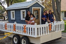 The Morales family rode on the Lakeshore Habitat parade float down Columbia Avenue to their new home at 132 E. 37th St., where an outdoor dedication was held.