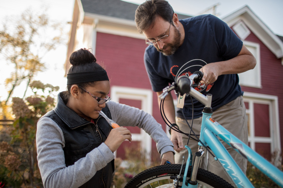 Lilyana Coleman, left, gets help from Jeff Hutchinson, right, adjusting her brakes.