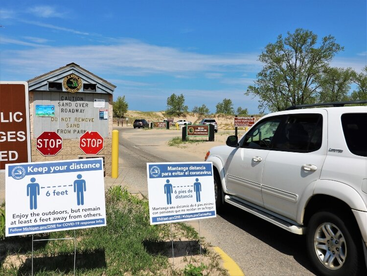 Coronavirus recommendations greet visitors to state parks in Holland and Grand Haven.