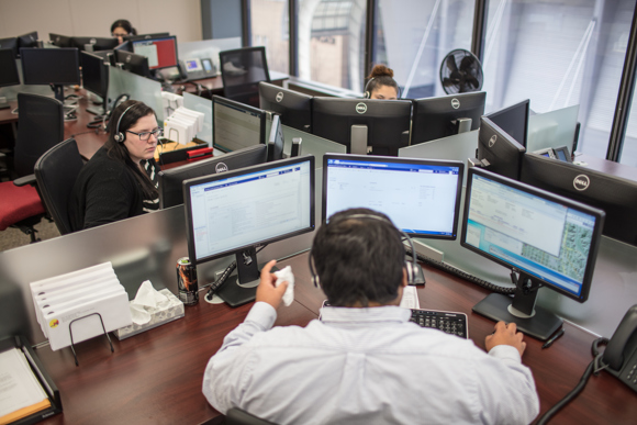 A bank of screens helps operators navigate city systems for residents calling for help.