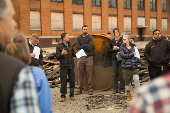 Justin Beene, second from the left, speaks at the the site of Rising Grinds.