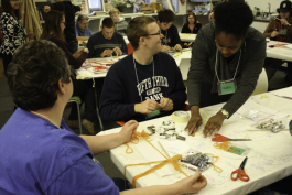 Volunteers help individuals with disabilities create art during Artists Creating Together's Adult Art Class.