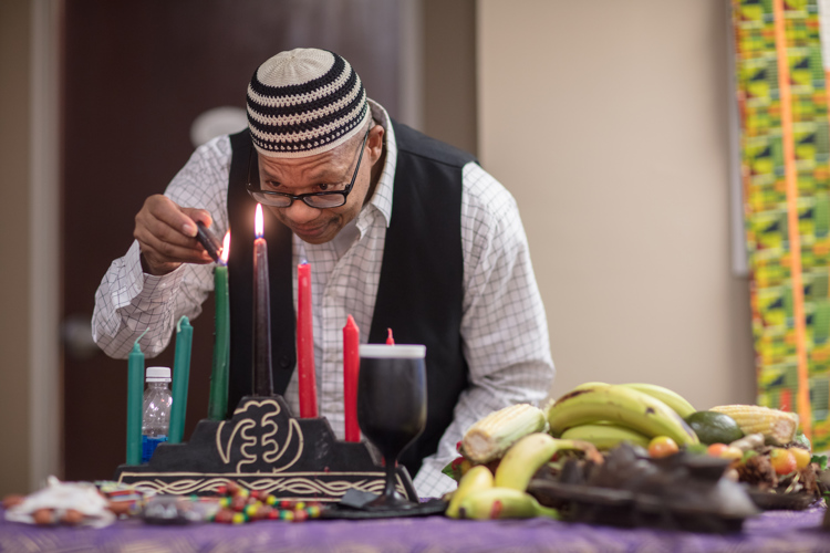 George Bayard lights Kwanzaa candles at the museum to celebrate the holiday.