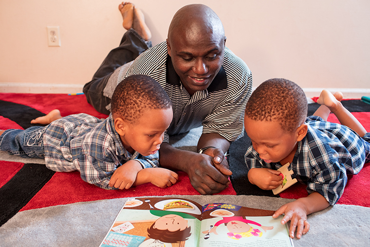Tetusa Ndalamba works on reading with his daycare kids.