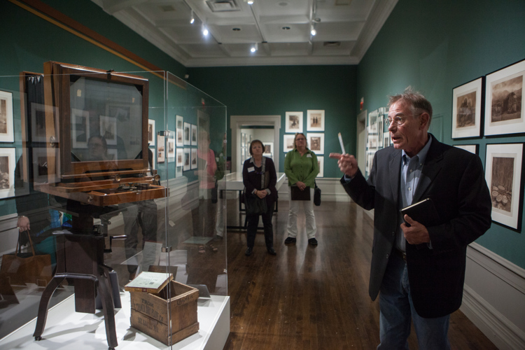 Curator Ben Mitchell points to a camera and other artifacts that accompany the photography exhibition.