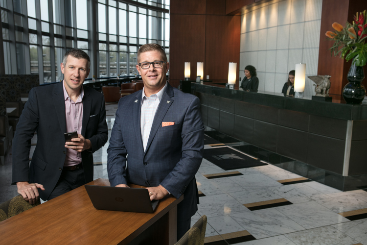 Josh Serba, left, and Brian Behler, right, of JW Marriott use technology to make a better hotel.