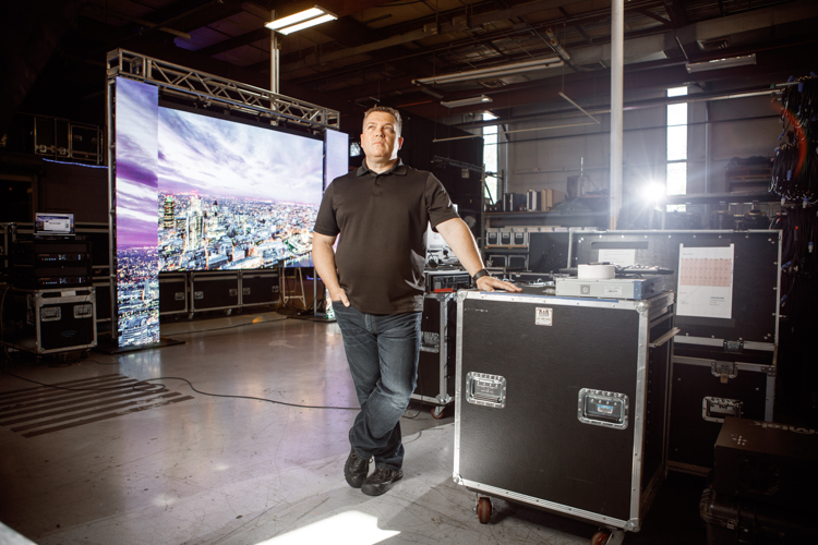 Todd Ernst stands in front of a massive backlit LED set up by LiveSpace.