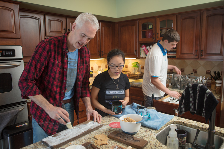 A transracial family, Bill Boersma, left, bakes cookies with kids Liana, middle, and Curran, right.