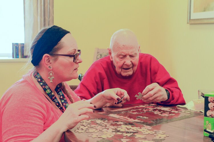 Sandy Loveless, a certified nurses aide, (left) and William Schavey work on a puzzle together at the LifeCircles PACE Hub in Holland Township on a recent afternoon.