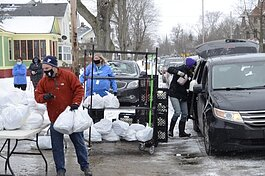 Muskegon YMCA volunteers distribute bags of food to those in need.