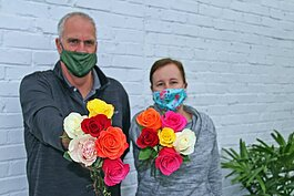 Dons Flowers and Gifts President Douglas J. Vos and office manager Katie DenHerder prepare to give away 3,500 roses to customers, so they can gift the flowers to friends and family in an effort to lift community spirits during the COVID-19 pandemic.