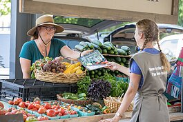 A Farmers Market Food Navigator interacts with a market patron.