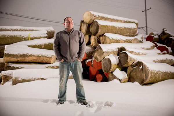 KC Weaver stands in front of stacks of curing elm wood.