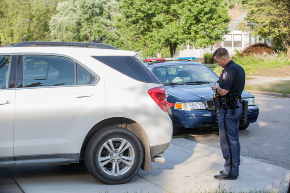 Officer Ryan Manser checks ownership history of a car while on a call.
