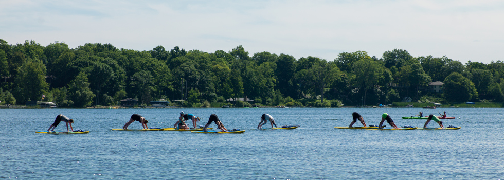 Stand up paddle board yoga on Reeds Lake with Funky Buddha Yoga.