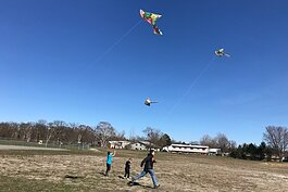 Kids fly kites at a sports gear giveaway at the Kinross Recreation Center.