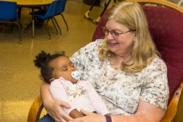 Kathy McNinch with a child at the Kalamazoo Drop-In Child Care Center.