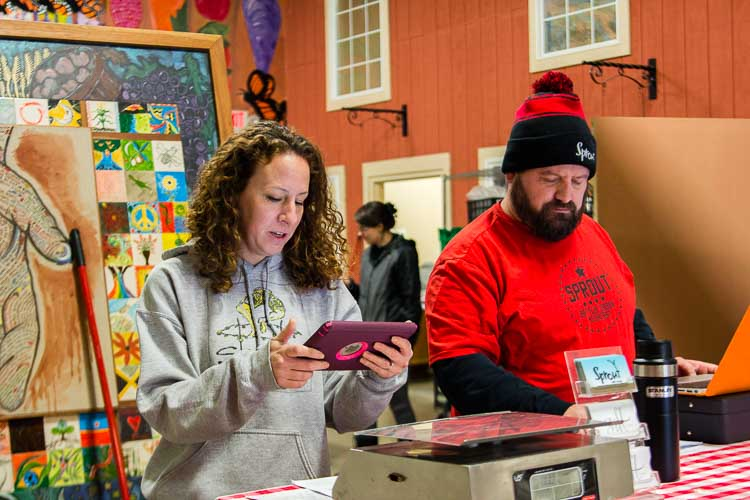 Lydia Marucco and Jeremy Andrews serve customers at Sprout's retail food store.